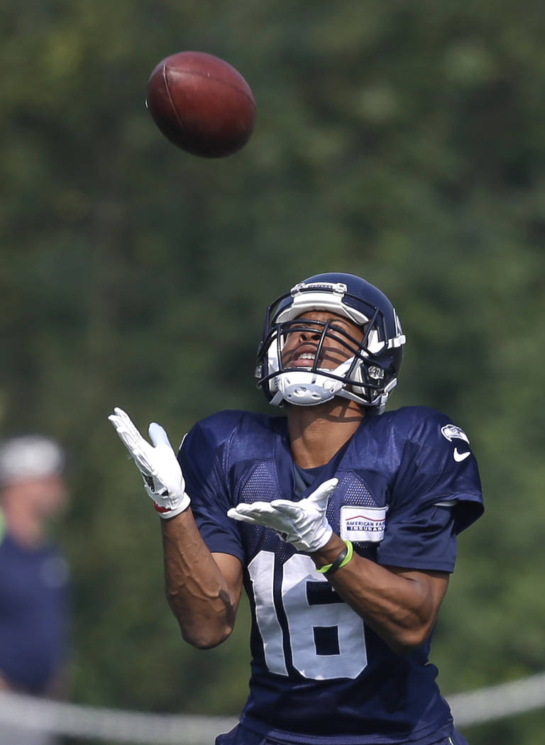 Seattle Seahawks' Tyler Lockett reaches to catch a ball during an NFL football training camp Friday, Aug. 4, 2017, in Renton, Wash. (AP Photo/Elaine Thompson)