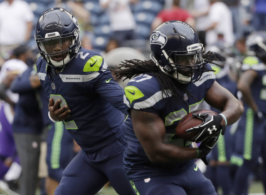 Seattle Seahawks quarterback Trevone Boykin, left, hands off the the ball to running back Eddie Lacy during pregame warmups before NFL football preseason game against the Minnesota Vikings, Friday ...