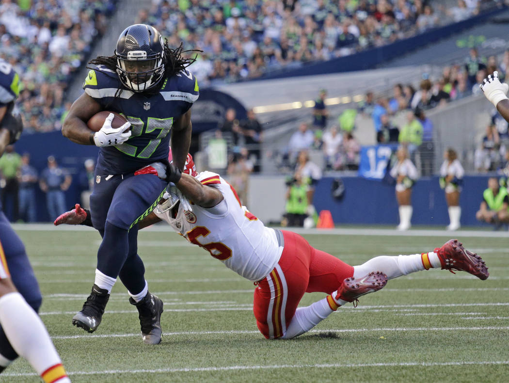 Seattle Seahawks running back Eddie Lacy, left, breaks a tackle by Kansas City Chiefs inside linebacker Derrick Johnson, right, during the first half of an NFL football preseason game, Friday, Aug ...