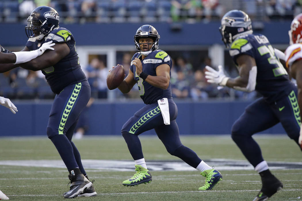Seattle Seahawks quarterback Russell Wilson looks to pass against the Kansas City Chiefs in the second half of an NFL football preseason game, Friday, Aug. 25, 2017, in Seattle. (AP Photo/Elaine T ...