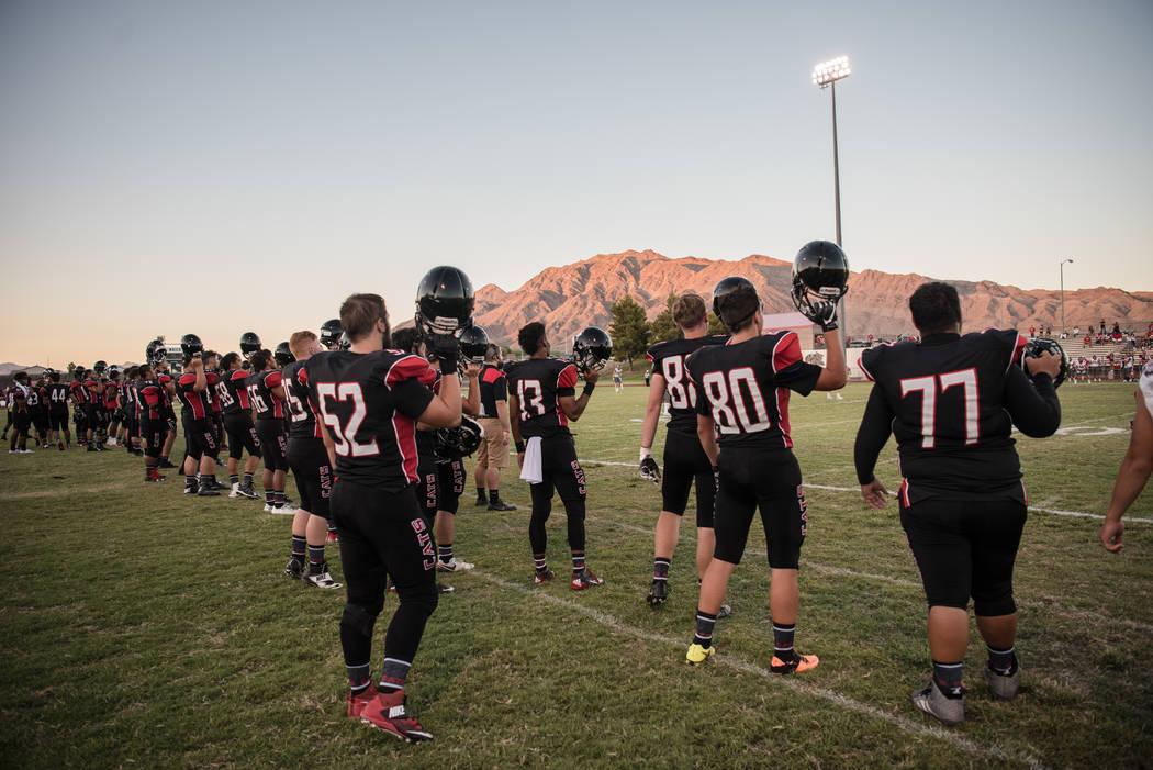 The Las Vegas High School football team holds their helmets up as kickoff begins at Las Vegas High School on Friday, Aug. 25, 2017, in Las Vegas. Morgan Lieberman Las Vegas Review-Journal