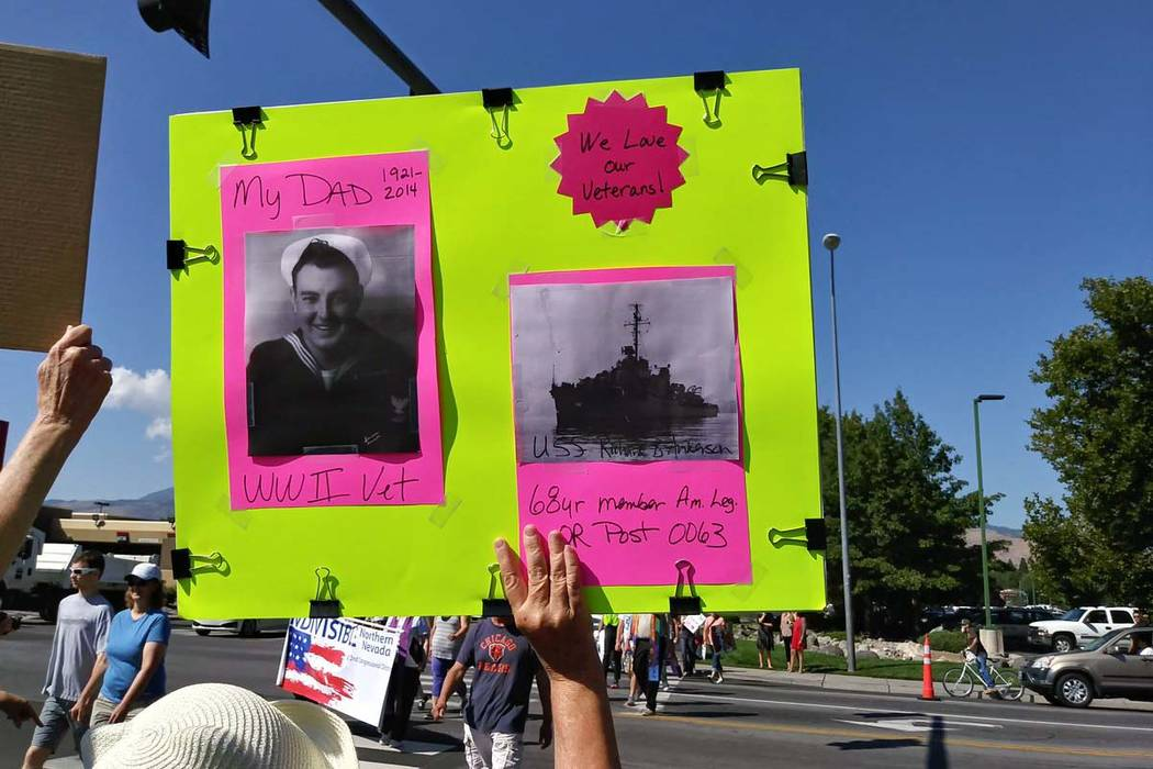 A woman holds a sign supporting veterans at the Reno-Sparks Convention Center in Reno before President Donald Trump's arrival to speak at the American Legion's annual convention, Wednesday, Aug. 2 ...