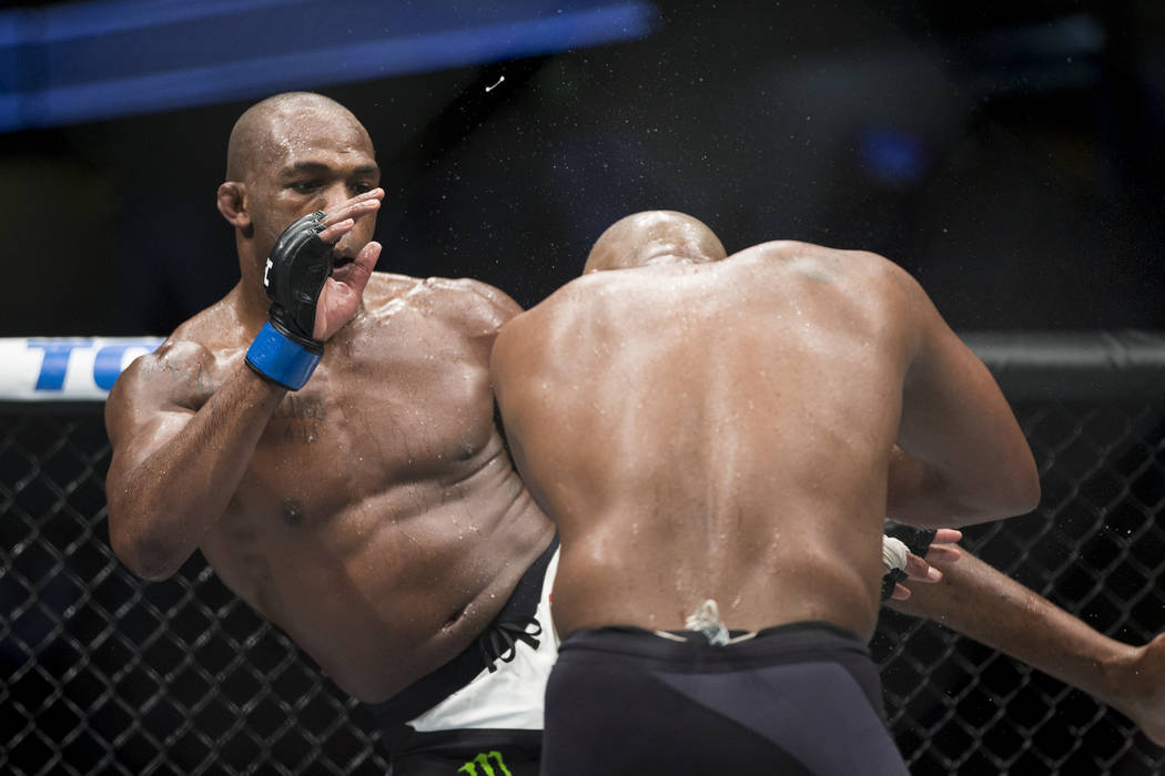 Jon Jones, left, connects a left kick against Daniel Cormier before following with punches and a knockout for a win in the light heavyweight title bout during UFC 214 at the Honda Center in Anahei ...