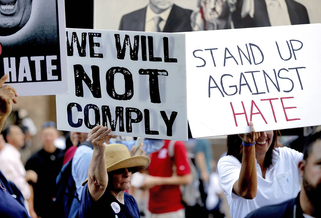 People protest outside the Phoenix Convention Center, Tuesday, Aug. 22, 2017, in Phoenix. Protests were held against President Donald Trump as planned to host a rally inside the convention center. ...
