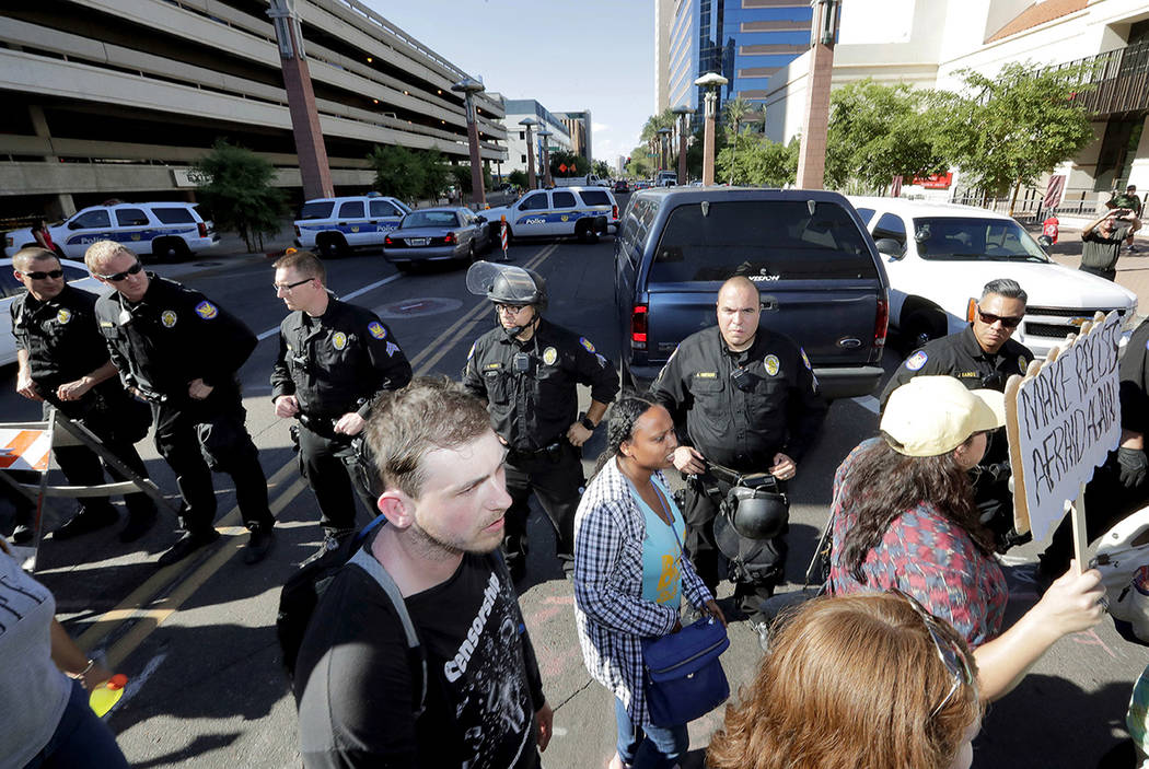 Protesters march past Phoenix police officers outside the Phoenix Convention Center, Tuesday, Aug. 22, 2017, in Phoenix. Protests were held against President Donald Trump as he planned to host a r ...