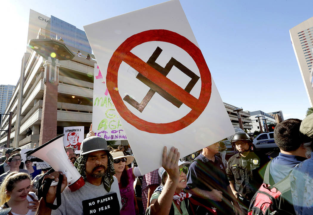 People protest outside the Phoenix Convention Center, Tuesday, Aug. 22, 2017, in Phoenix. Protests were held against President Donald Trump as he planned to host a rally inside the convention cent ...