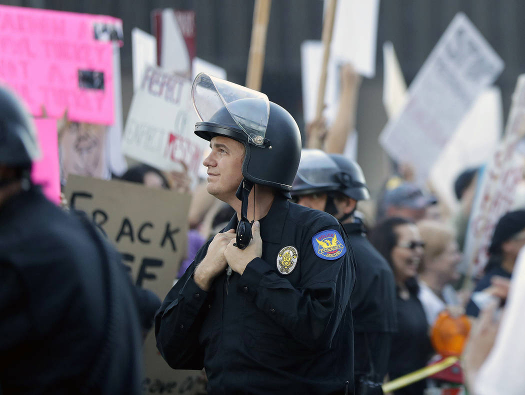 A Phoenix police officer stands in the street as people protest outside the Phoenix Convention Center, Tuesday, Aug. 22, 2017, in Phoenix. Protests were held against President Trump as he hosted a ...