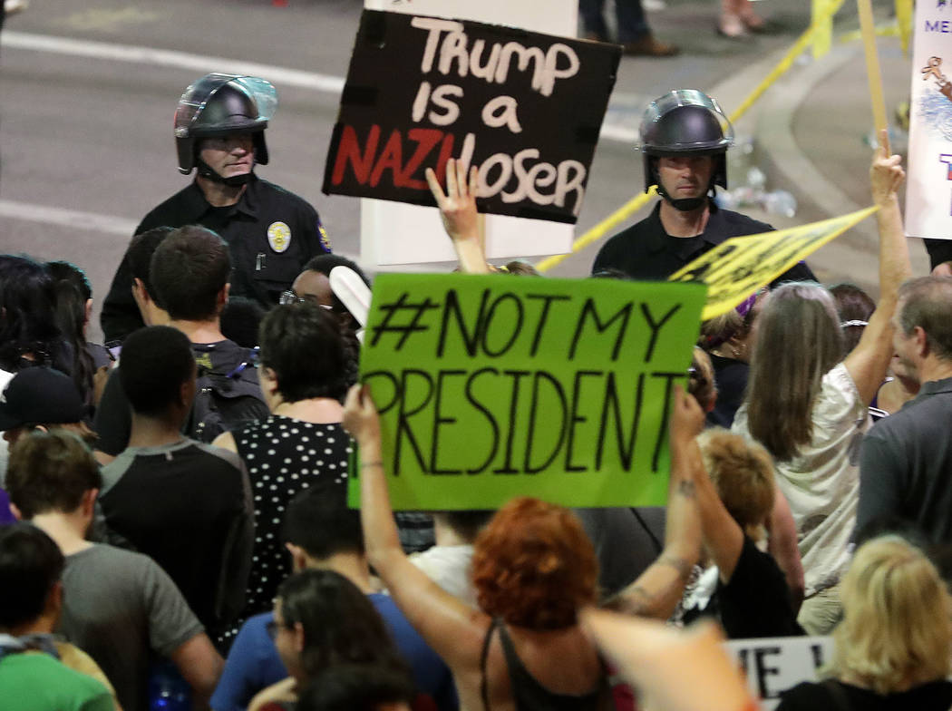 People protest outside the Phoenix Convention Center, Tuesday, Aug. 22, 2017, in Phoenix. Protests were held against President Donald Trump as he hosted a rally inside the convention center. (AP P ...