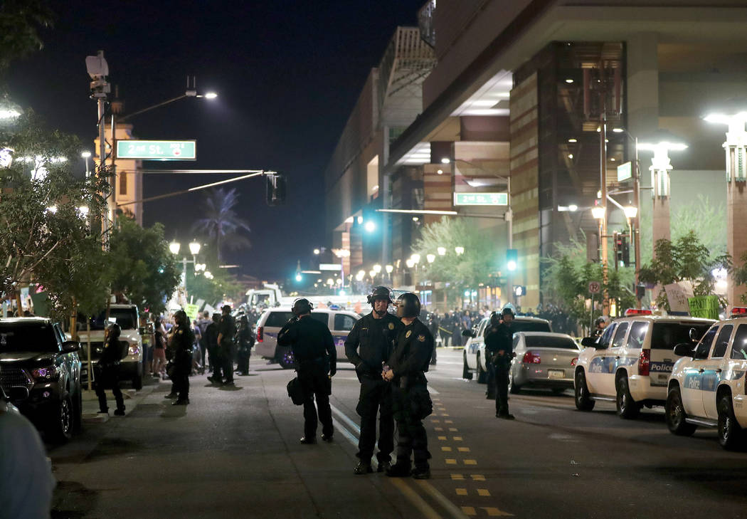 Phoenix police keep the streets clear as people protest outside the Phoenix Convention Center, Tuesday, Aug. 22, 2017, in Phoenix. Protests were held against President Donald Trump as he hosted a  ...