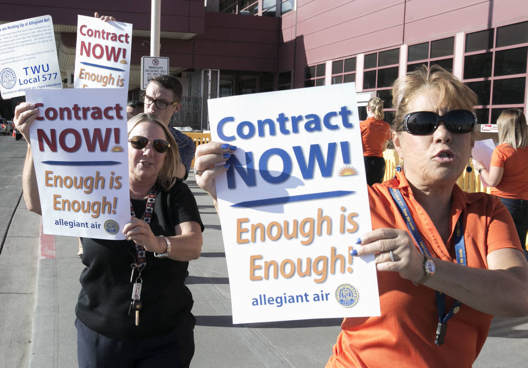 Allegiant Air flight attendants, including Kim Wood, right, picket in front of McCarran International Airport to highlight union efforts to settle a six-year contract fight on Wednesday, Aug. 23,  ...