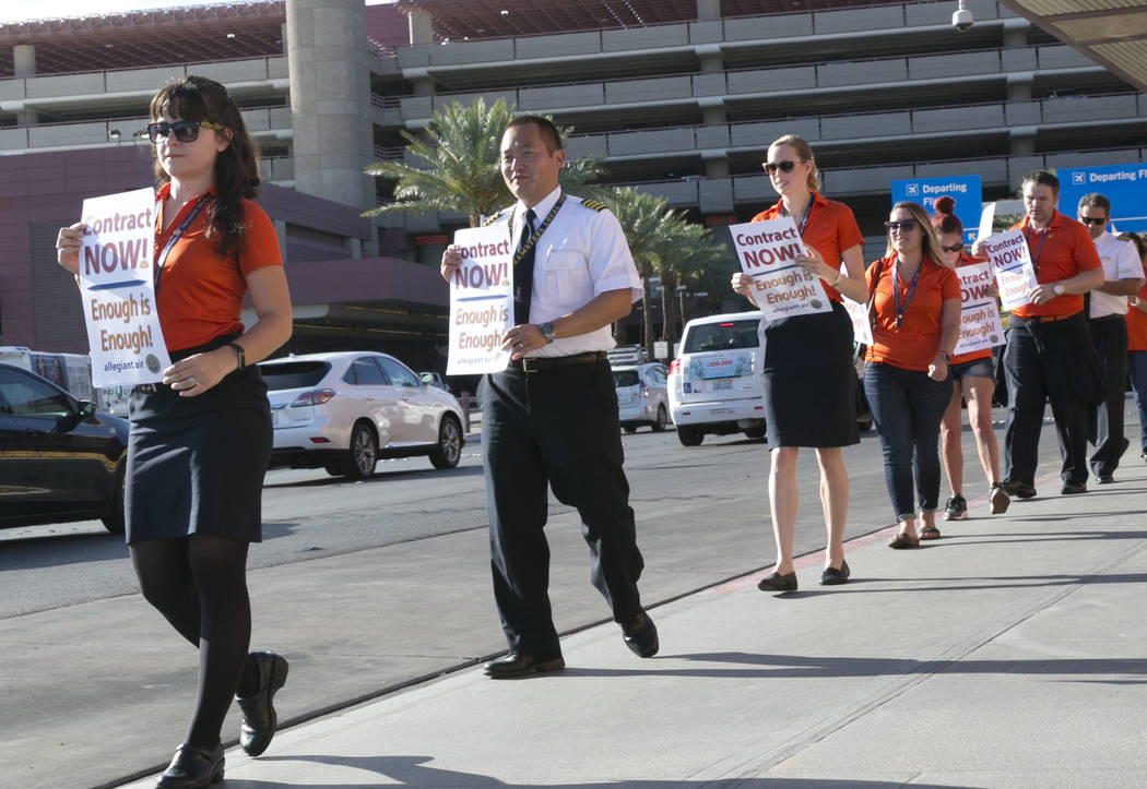 Allegiant Air flight attendants, including, from left, Elise Gordon, Alex Kim and Molly Perry picket in front of McCarran International Airport to highlight union efforts to settle a six-year cont ...