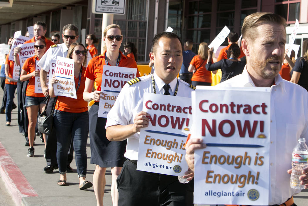 Allegiant Air flight attendants, including, from right, Joe Mayfield, Alex Kim and Molly Perry picket in front of McCarran International Airport to highlight union efforts to settle a six-year con ...