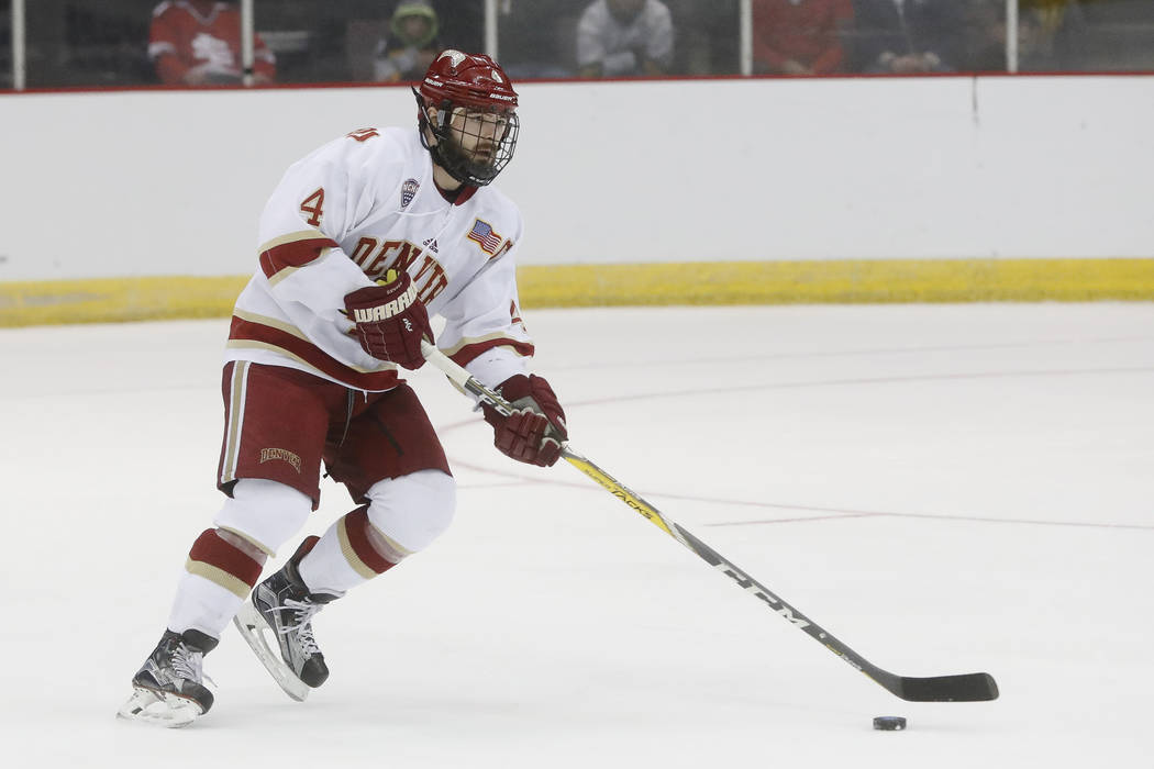 Denver's Will Butcher skates the puck up the ice during the first period in the regional semifinals of the NCAA college hockey tournament against Michigan Tech, Saturday, March 25, 2017, in Cincin ...