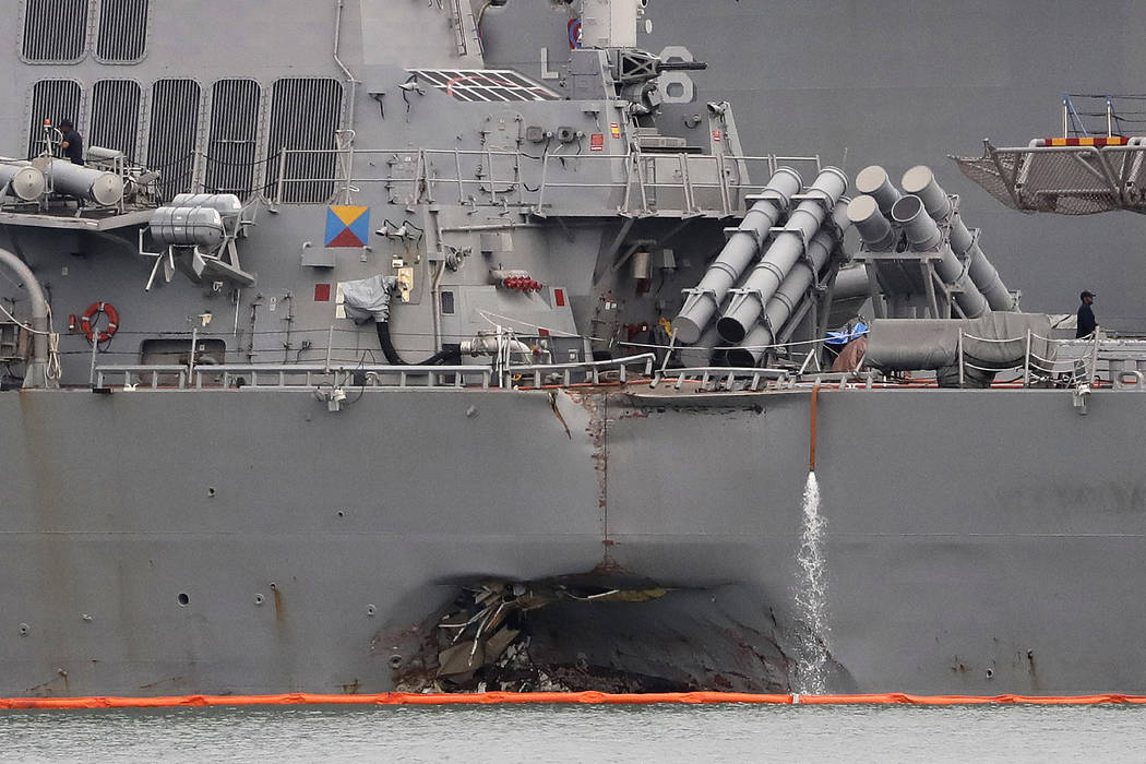 The damaged port aft hull of the USS John S. McCain, is visible while docked at Singapore's Changi naval base on Tuesday, Aug. 22, 2017 in Singapore. The focus of the search for the U.S. sailors m ...