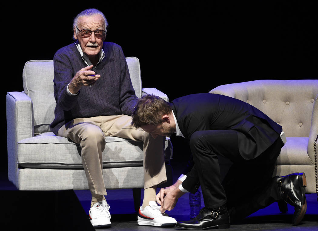 """Host Chris Hardwick, right, pays tribute to comic book writer Stan Lee by tying his shoes onstage at the """"Extraordinary: Stan Lee"""" tribute event at the Saban Theatre on Tuesday,  ..."""