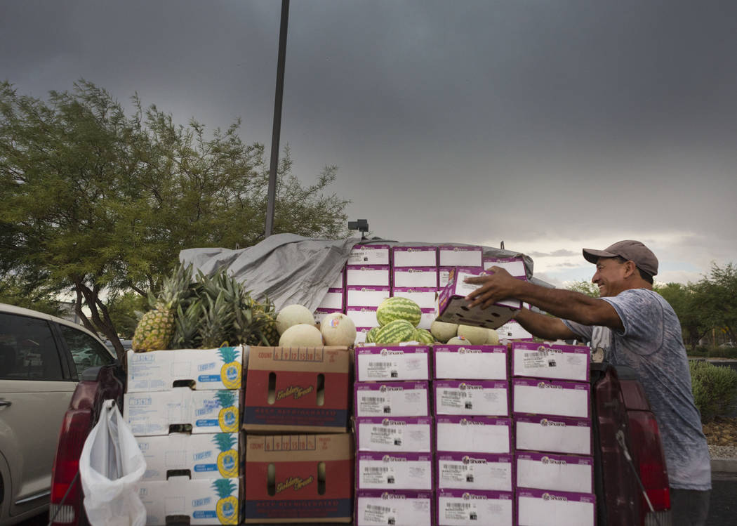 Sylvester Torres moves his Californian fruit to cover from the rain off of Silverado Ranch Blvd. and Bermuda Road in Las Vegas, Wednesday, Aug. 23, 2017. Elizabeth Brumley Las Vegas Review-Journal