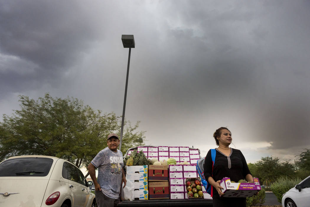 Californian fruit salesman Sylvester Torres , left, and Florence Khan who is his last customer of the day because of the rain off of Silverado Ranch Boulevard and Bermuda Road in Las Vegas, Wednes ...