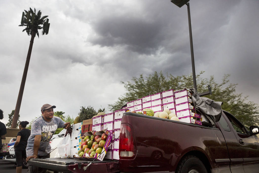 Sylvester Torres moves his Californian fruit to cover from the rain off of Silverado Ranch Boulevard and Bermuda Road in Las Vegas, Wednesday, Aug. 23, 2017. Elizabeth Brumley Las Vegas Review-Journal