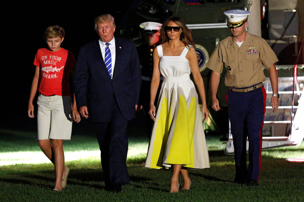 President Donald Trump walks with first lady Melania Trump and their son Barron, left, on the South Lawn of the White House upon their return to Washington, D.C., after a vacation in Bedminster, N ...