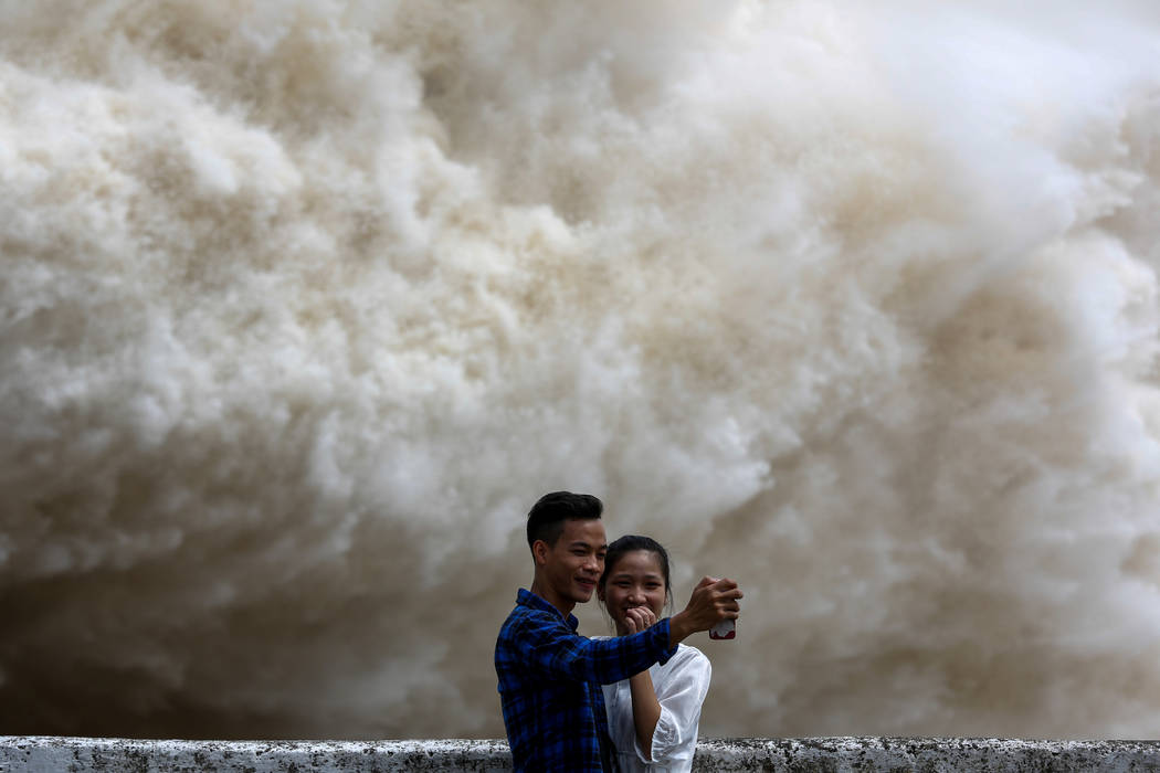A couple takes a selfie as Hoa Binh hydroelectric power plant opens the flood gates after a heavy rainfall caused by Talas typhoon in Hoa Binh province, outside Hanoi, Vietnam July 20, 2017. REUTE ...