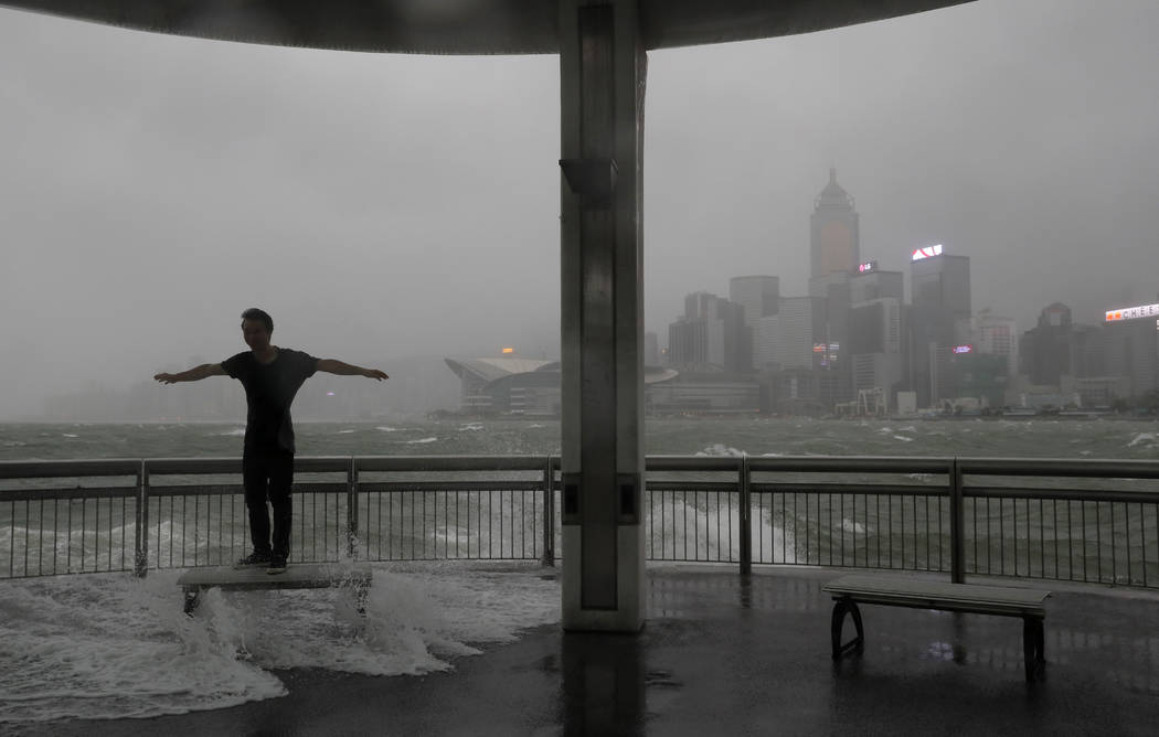 A man plays with strong wind caused by typhoon Hato on the waterfront of Victoria Habour in Hong Kong, Wednesday, Aug. 23, 2017. A powerful typhoon barreled into Hong Kong on Wednesday, forcing of ...