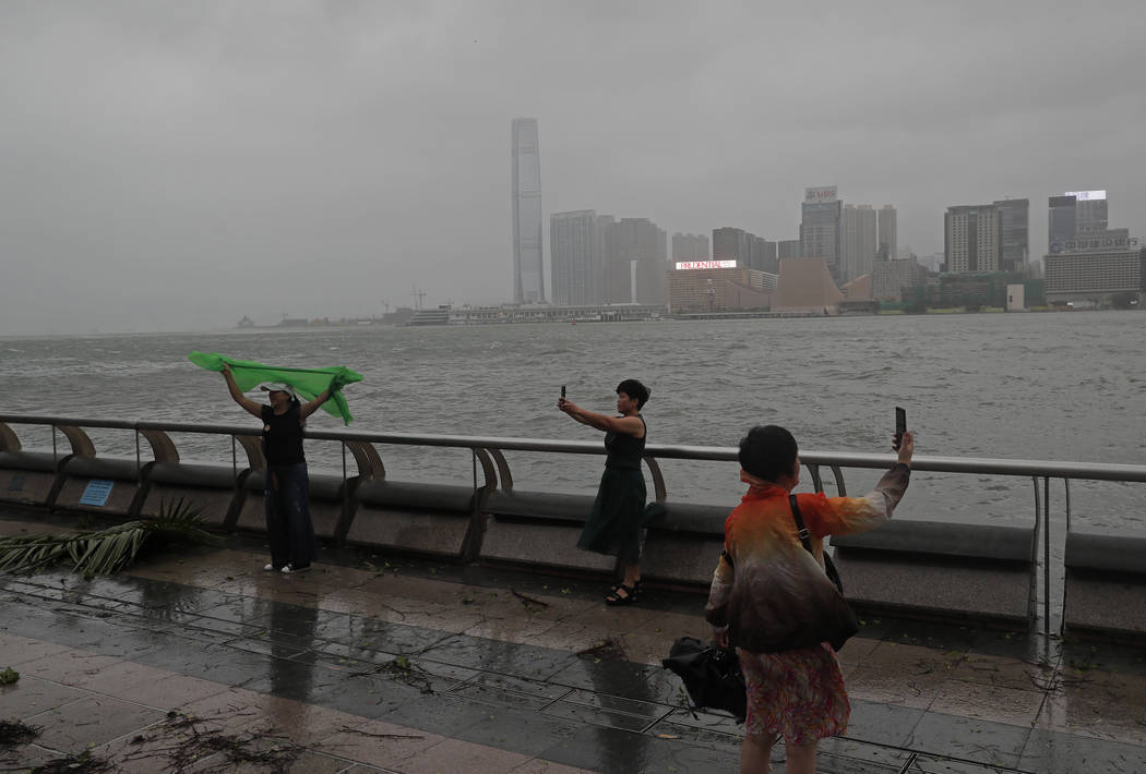 Mainland Chinese tourists take pictures against the wind caused by Typhoon Hato on the waterfront of Victoria Habour in Hong Kong, Wednesday, Aug. 23, 2017. A powerful typhoon barreled into Hong K ...