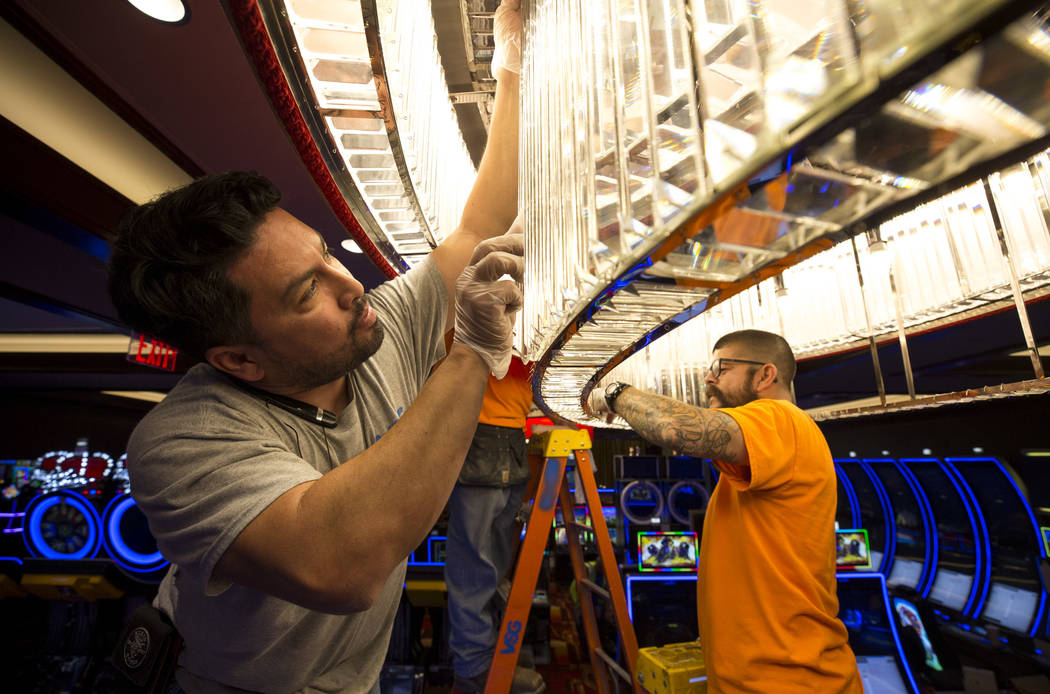 Marvin Mendez, left, and Lenny Paz, electricians with Volta Systems Group, work on a chandelier during renovations at the Golden Gate hotel-casino on Thursday, Aug. 25, 2017, in downtown Las Vegas ...