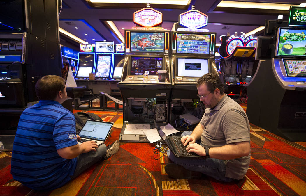 Evotek technician Todd Hoaglin, left, and Golden Gate network administrator Jeremy Isom prepare slot machines for play during renovations at the Golden Gate hotel-casino on Thursday, Aug. 25, 2017 ...