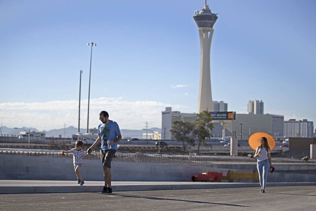 Alek May, 3, from left, with his parents Cory and Mirella Garcia walk a portion of the new Martin Luther King Boulevard, which is being built as part of Project Neon in Las Vegas, on Saturday, Aug ...