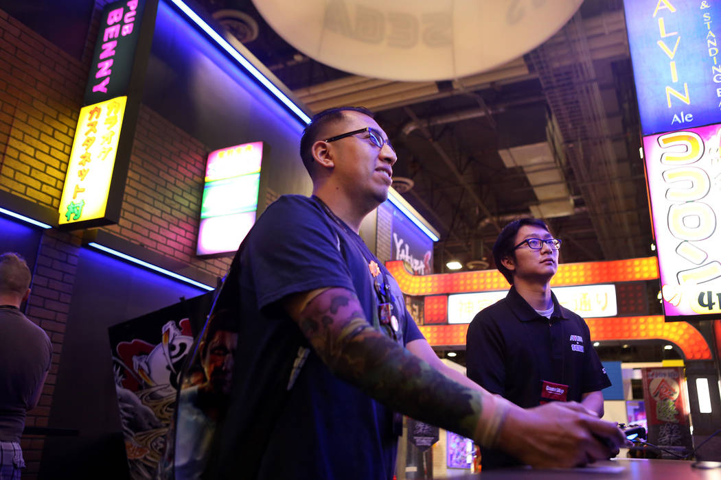 Robert Uck, left, plays Yakuza Kiwami while Jonathan Mac watches during the 2017 GameStop Expo at the Sands Expo and Convention Center, Sunday, Aug. 27, 2017 . Elizabeth Brumley Las Vegas Review-J ...