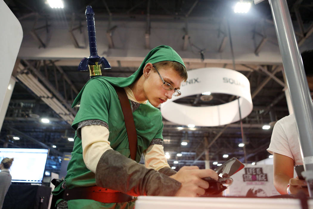 Derrek Buck tests an upcoming game, Metroid: Samus Returns, on a Nintendo 3DS handheld game console during the 2017 GameStop Expo at the Sands Expo and Convention Center, Sunday, Aug. 27, 2017 . E ...