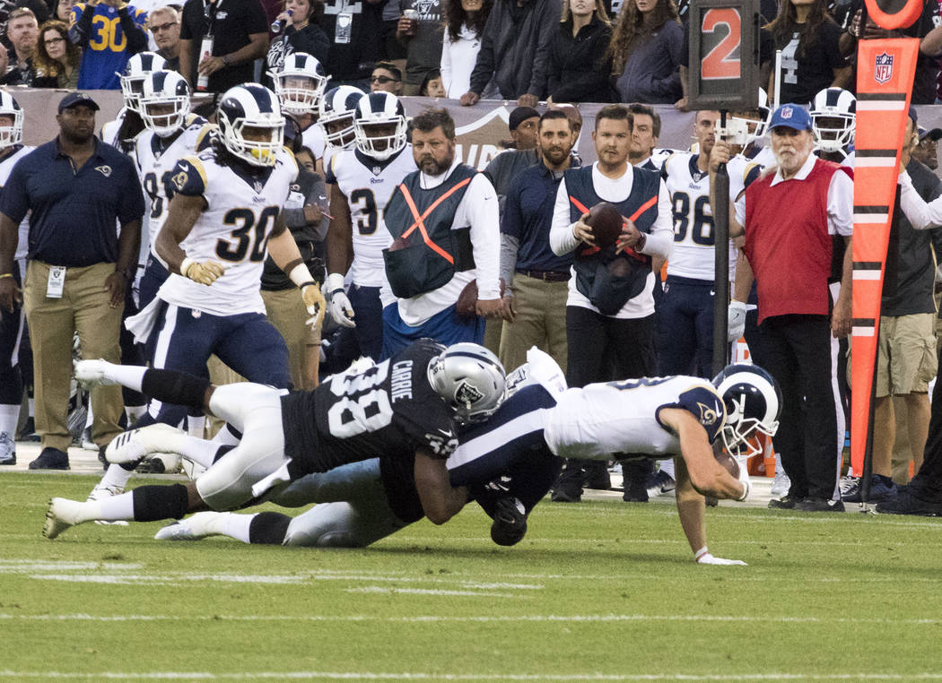 Los Angeles Rams wide receiver Cooper Kupp (18) is tackled by Oakland Raiders strong safety T.J. Carrie (38) during the second quarter of a NFL preseason football game in Oakland, Calif., Saturday ...