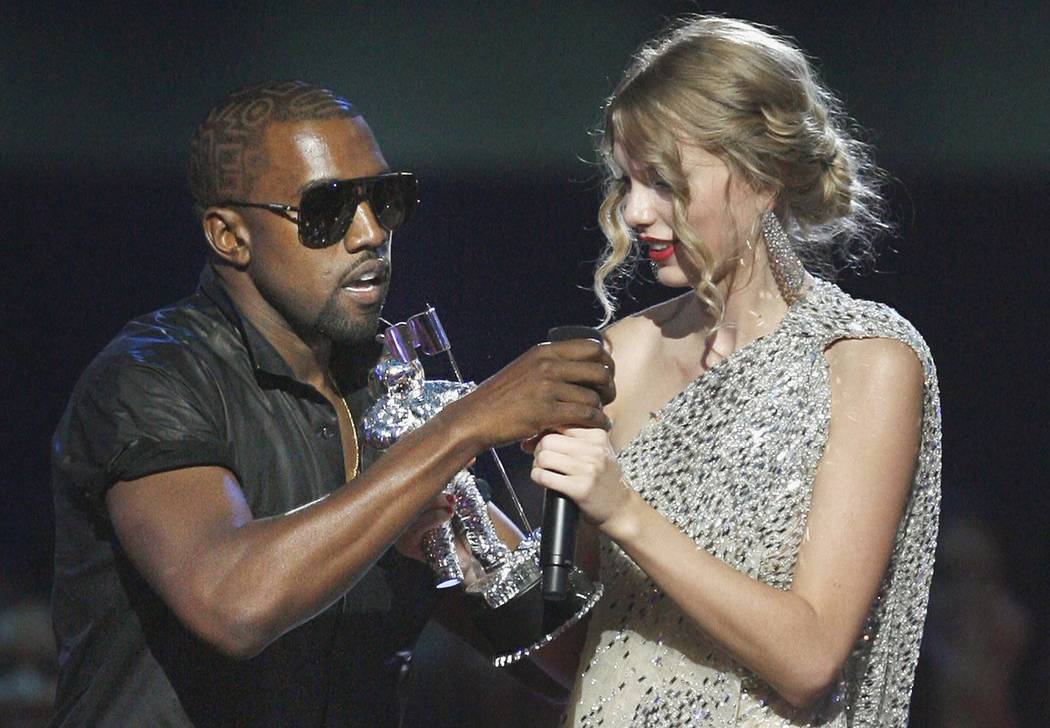 """FILE - In this Sept. 13, 2009 file photo, singer Kanye West takes the microphone from singer Taylor Swift as she accepts the """"Best Female Video"""" award during the MTV Video Music  ..."""