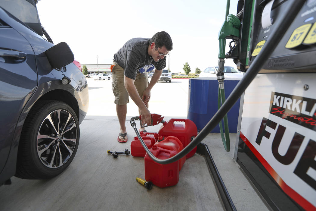 Chris Mathew fills his vehicle and five gas cans at Costco in preparation for tropical weather on Wednesday, Aug. 23, 2017, in Pearland, Texas. The U.S. National Hurricane Center said the tropical ...