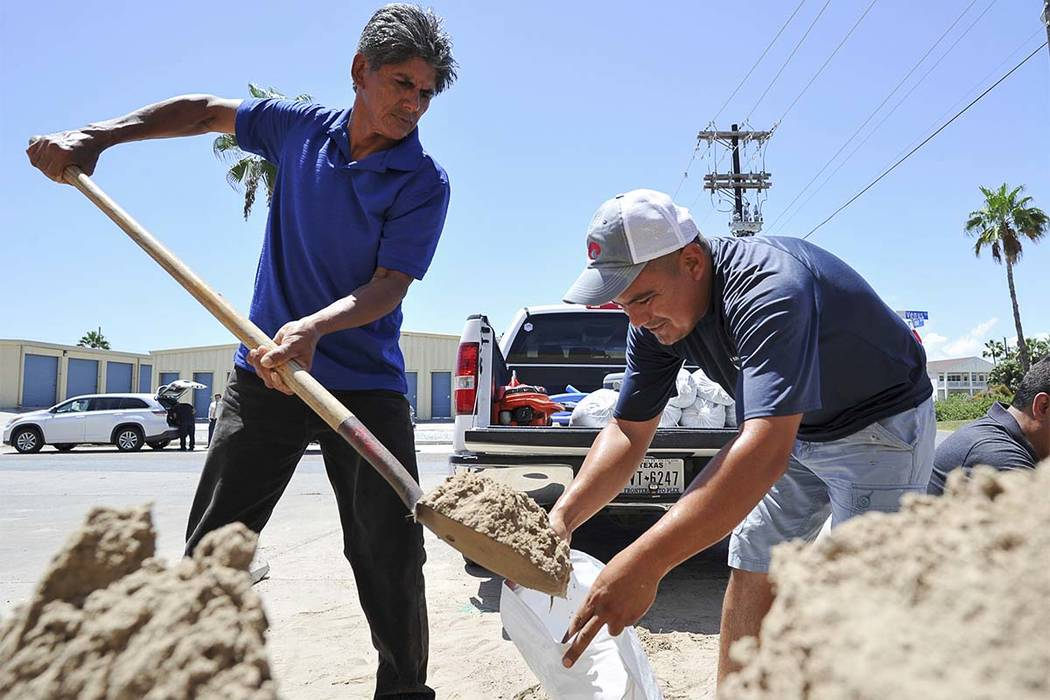 Leo Sermiento, left, and Emilio Gutierrez fill sandbags in preparation of a tropical system on Wednesday, Aug. 23, 2017, on South Padre Island, Texas. Texas Gov. Greg Abbott has ordered the State  ...