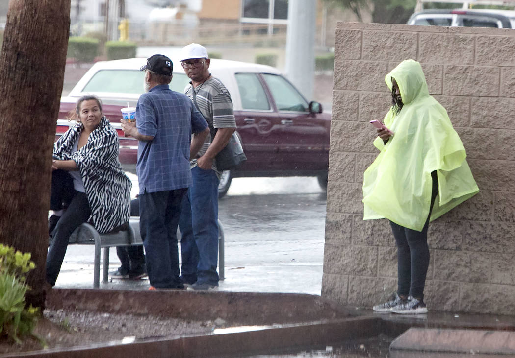 Commuters wait for a bus under a tree on Lake Mead Boulevard during a heavy rainfall in Las Vegas on Thursday, Aug. 24, 2017. (Bizuayehu Tesfaye/Las Vegas Review-Journal) @bizutesfaye