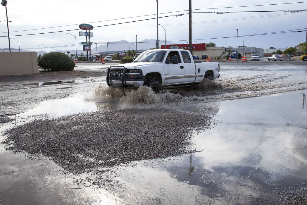 A motorist drives through a flooded parking lot near the intersection of East Cheyenne Avenue and North Las Vegas Boulevard in North Las Vegas on Thursday, Aug. 24, 2017. Richard Brian Las Vegas R ...