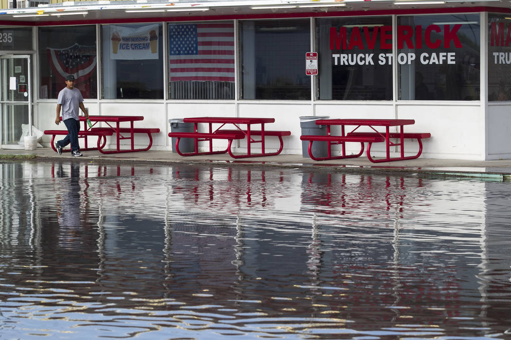 A man walks through a flooded parking lot near the intersection of East Cheyenne Avenue and North Las Vegas Boulevard in North Las Vegas on Thursday, Aug. 24, 2017. Richard Brian Las Vegas Review- ...