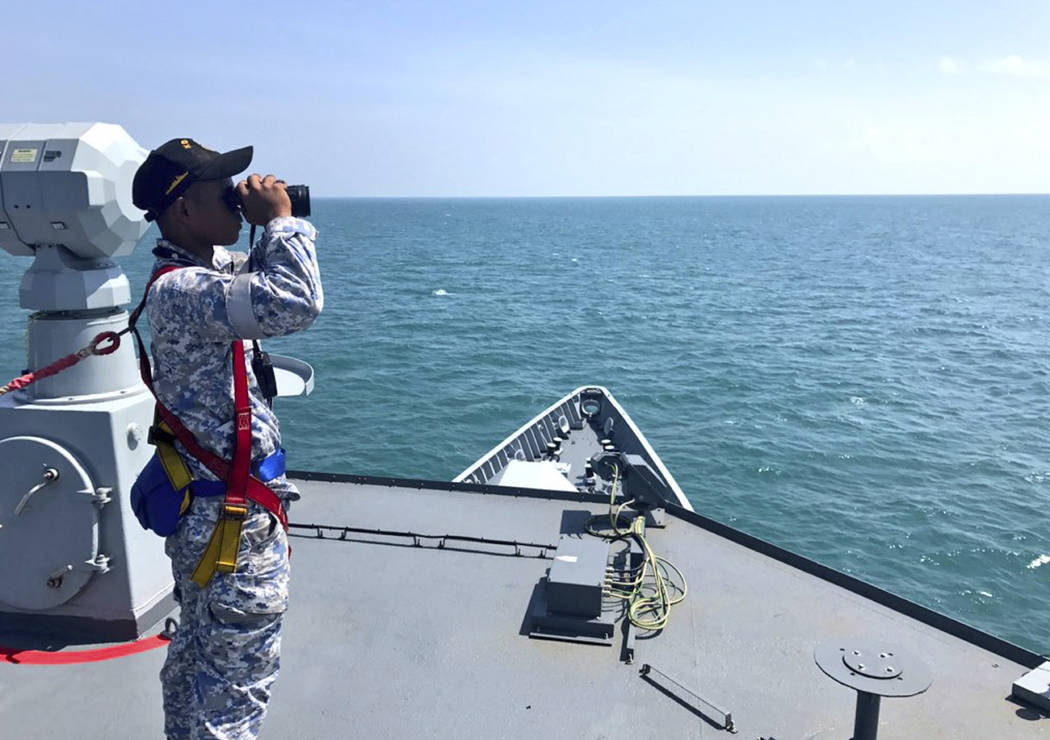 In this photo released by the Royal Malaysian Navy, a Royal Malaysian Navy sailor scans the sea for missing sailors  from the USS John S. McCain off the Johor coast of Malaysia, Wednesday, Aug. 23 ...