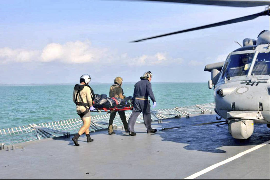 In this photo released by the Royal Malaysian Navy, an unidentified body recovered by the Royal Malaysian Navy is transferred to a U.S. Navy helicopter off the Johor coast of Malaysia, Wednesday,  ...