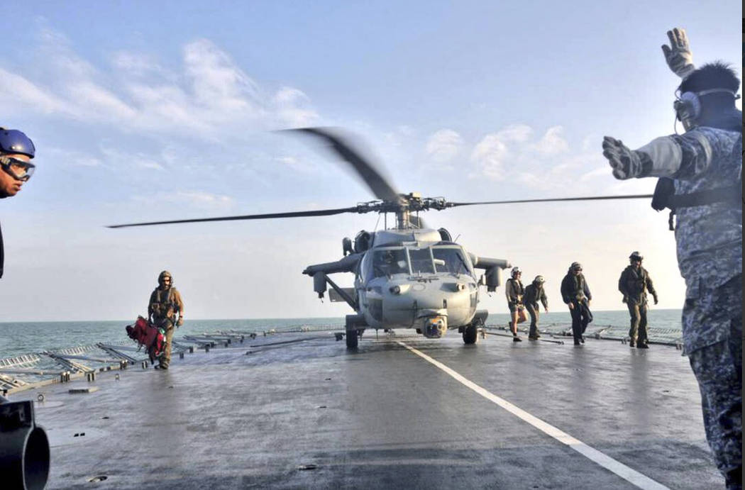 In this photo released by the Royal Malaysian Navy, a U.S. Navy helicopter lands to receive an unidentified body recovered by the Royal Malaysian Navy off the Johor coast of Malaysia, Wednesday, A ...
