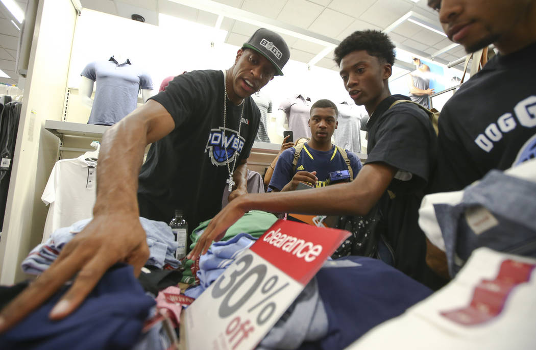 Former NBA player Jerome Williams, now a player in the Big 3 basketball league, left, helps Rason, 17, center, and Dwayne, 18, look for clothes during an event held by the Nevada Partnership for H ...