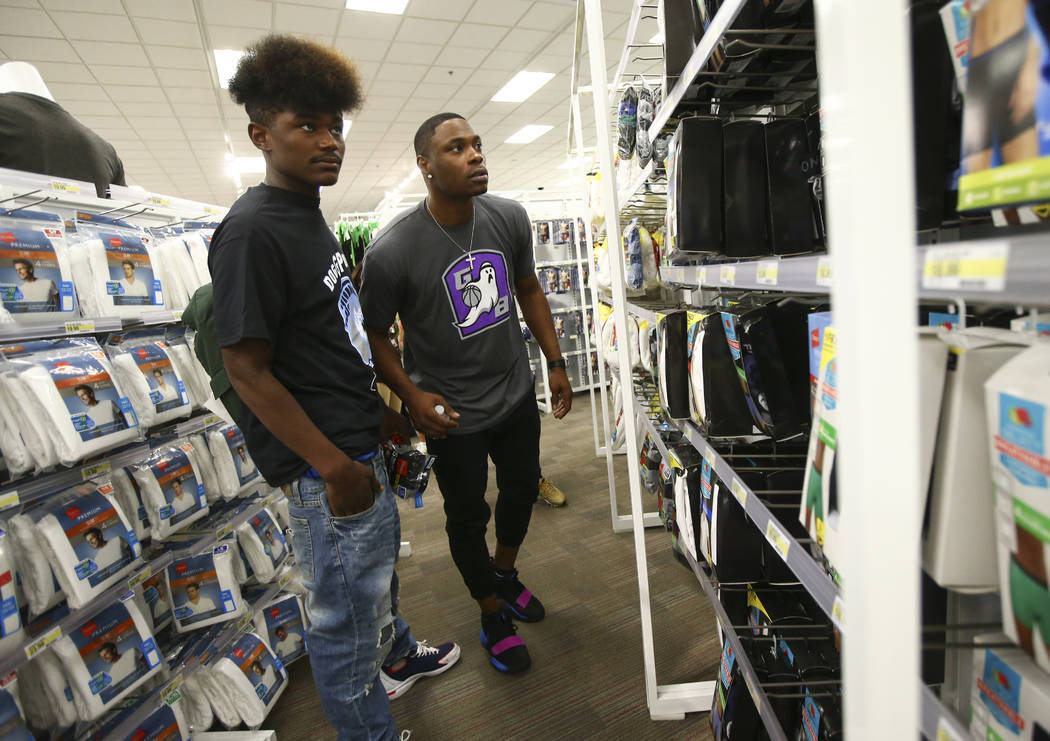 Former UNLV and NBA player Marcus Banks, now a player in the Big 3 basketball league, right, helps Dejuan Torain-Duntin, 18, look for clothes during an event held by the Nevada Partnership for Hom ...