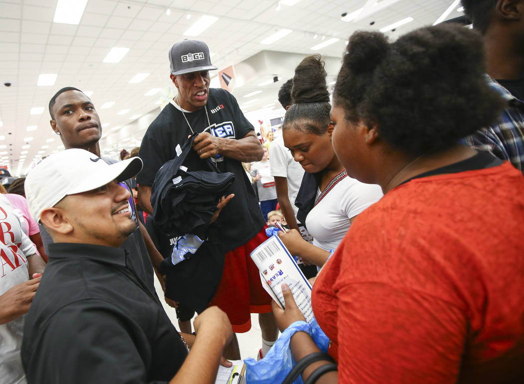 Rico Ocampo, lower left, with the Nevada Partnership for Homeless Youth, and former NBA player Jerome Williams, center, hand out shirts  during an event held by the Nevada Partnership for Homeless ...