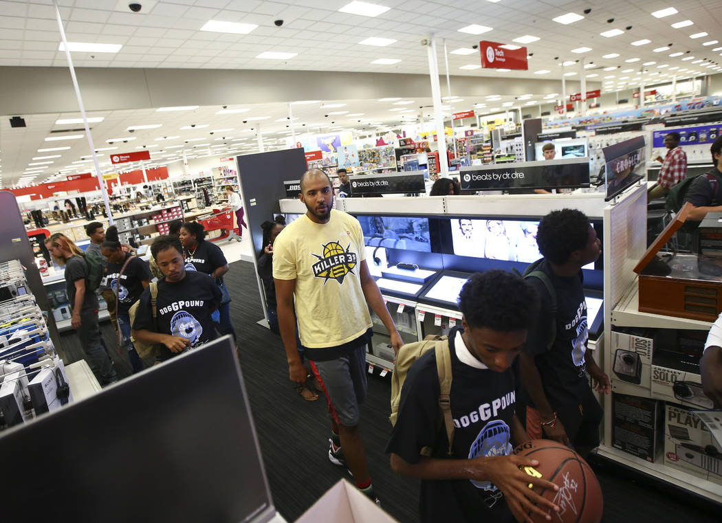 Players in the Big 3 basketball league, including former NBA player Brian Cook, center, help homeless children and young adults shop during an event held by the Nevada Partnership for Homeless You ...