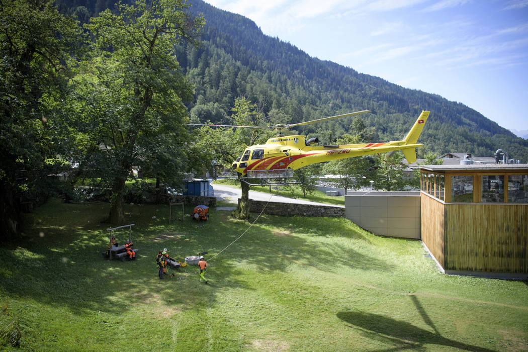 A search-and-rescue team is transported by a helicopter in the village of Bondo in Graubuenden in southern Switzerland, Thursday, Aug. 24, 2017. Police said eight people are still unaccounted for  ...