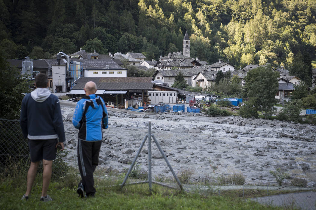 People watch the landslide that hit the village Bondo in Graubuenden in South Switzerland, Thursday, Aug. 24, 2017. (Gian Ehrenzeller/Keystone via AP)