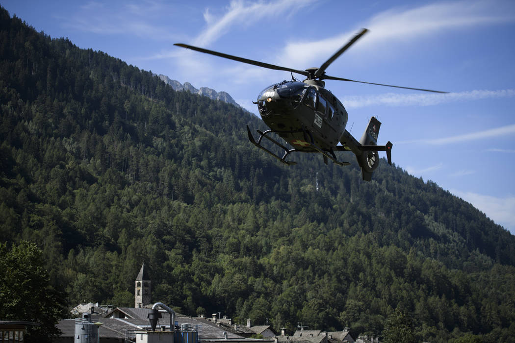 A police helicopter flies over the village Bondo in Graubuenden in southern Switzerland, Thursday, Aug. 24, 2017. (Gian Ehrenzeller/Keystone via AP)