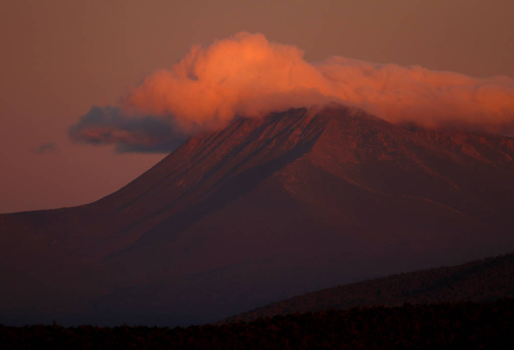 The first rays of sunlight color the clouds over Mount Katahdin in this view from the Katahdin Woods and Waters Scenic Byway outside Patten, Maine on  Monday, Aug. 7, 2017. (AP Photo/Robert F. Bukaty)