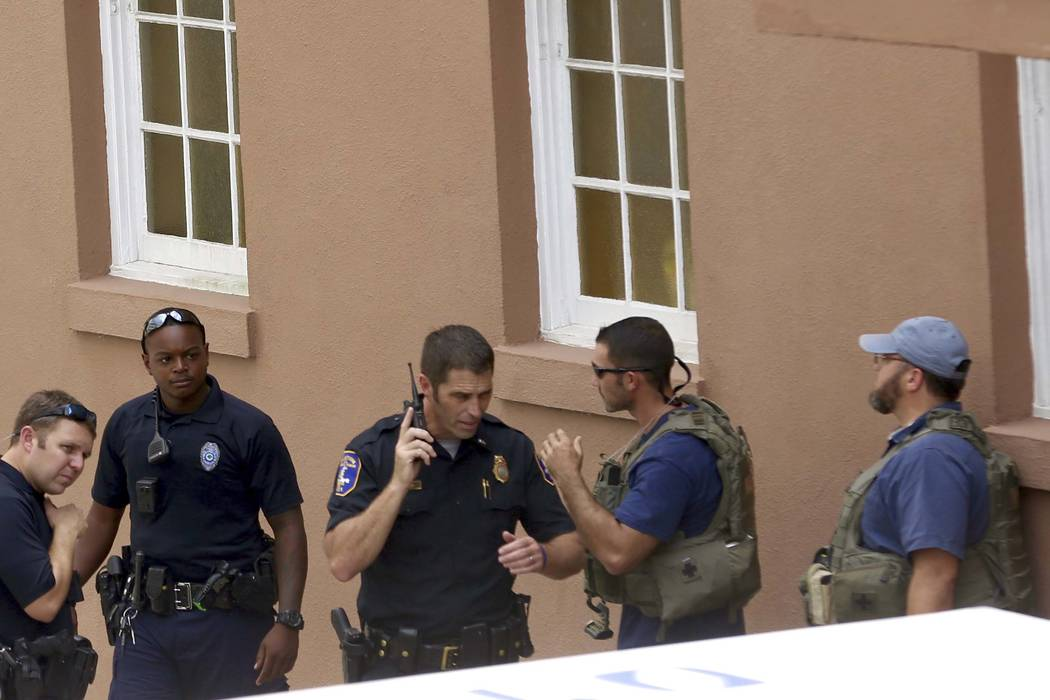 Police gather near the scene of a reported shooting in Charleston, S.C., on Thursday, Aug.24, 2017.  Authorities say a disgruntled employee shot one person and is holding hostages in a restaurant  ...